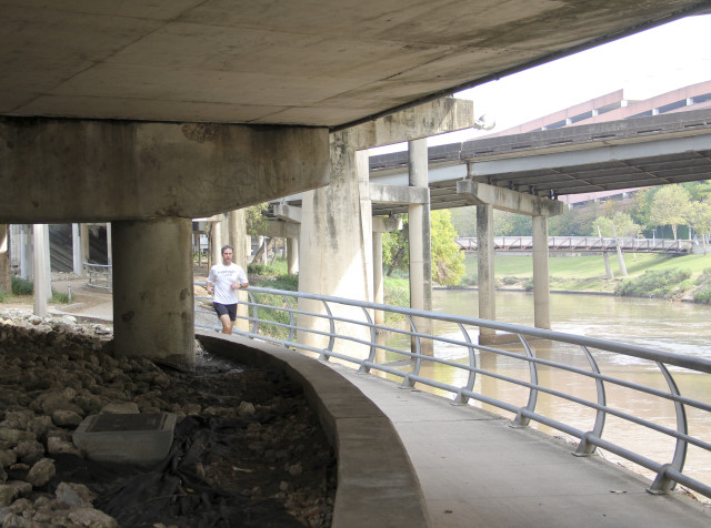 Jogger underneath freeway infrastructure on the trail along Buffalo Bayou. Photo: Allyn West.