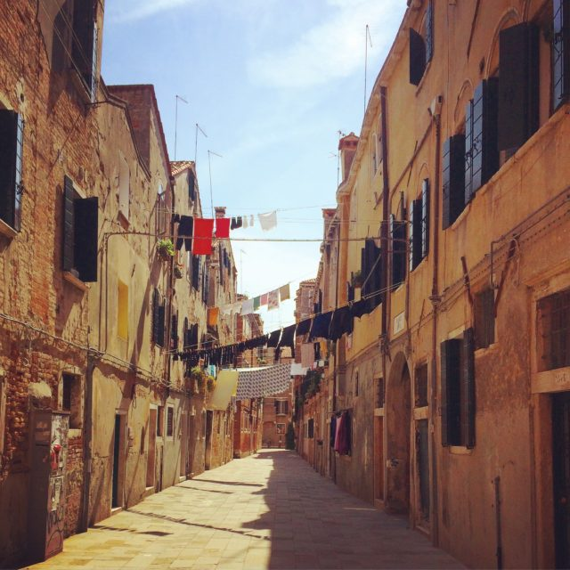An architect's black clothes dry above Calle del Formo, a Venetian side street. Photo: Daisy Ames.